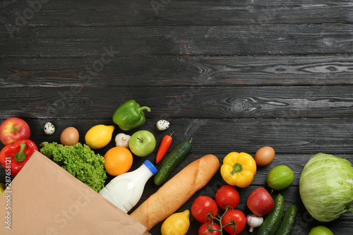 Cuadros en Lienzo Flat lay composition with overturned paper bag and groceries on black wooden background