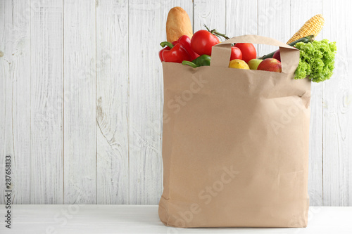 Shopping paper bag with different groceries on table against white wooden background. Space for text