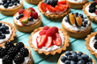 Many different berry tarts on blue wooden table. Delicious pastries