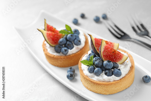 Foto op Canvas Bakkerij Tarts with blueberries and figs served on light table. Delicious pastries
