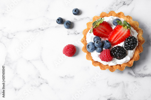 Top view of tart with different berries on marble table, space for text. Delicious pastries - 287658347
