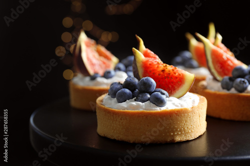 Fototapeta Tarts with blueberries and figs on black table against dark background, closeup. Delicious pastries obraz