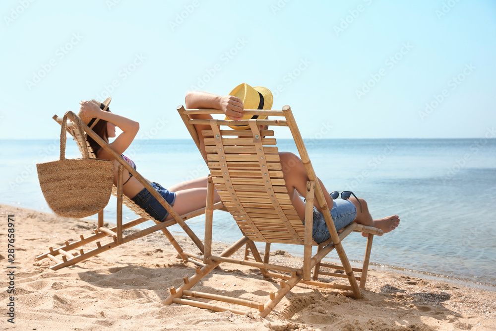 Fototapeta Young couple relaxing in deck chairs on beach