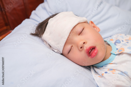 Cuadros en Lienzo Asian 3 - 4 years old toddler boy child gets high fever lying on bed with cold c