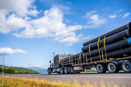 Black powerful big rig semi truck transporting plastic pipes fastened on step do Canvas Print