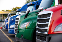 Different Make Big Rig Semi Trucks Tractors Stands In Row On Truck Stop Parking Lot Marked With Lines