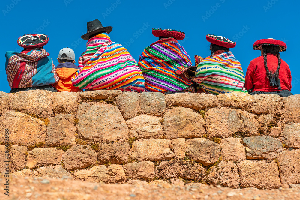 Fototapeta A group of Quechua indigenous women in traditional clothing and a young boy sitting and chatting on an ancient Inca wall in the archaeological site of Chinchero in the region of Cusco city, Peru.