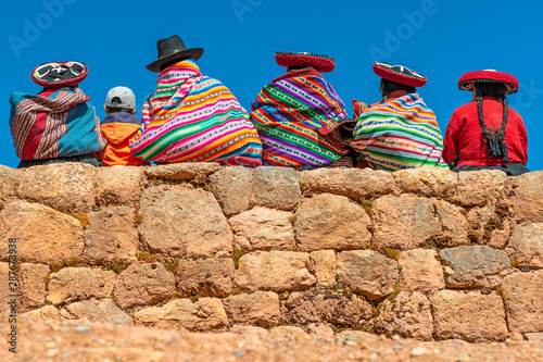Fotografía  A group of Quechua indigenous women in traditional clothing and a young boy sitting and chatting on an ancient Inca wall in the archaeological site of Chinchero in the region of Cusco city, Peru