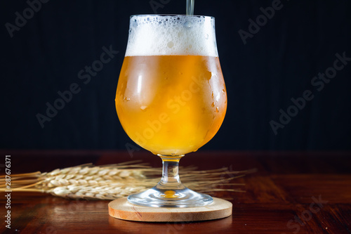Hazy IPA craft beer being poured into a tulip shaped beer glass. фототапет