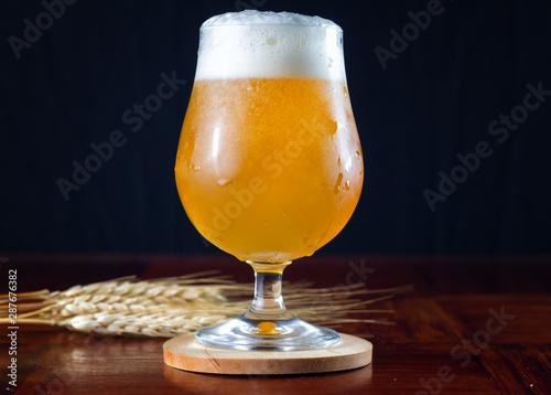 Fotografía Hazy IPA craft beer in a tulip shaped beer glass with lots of foamy head