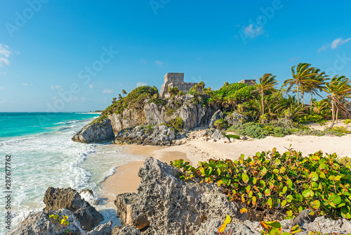 Fotografia, Obraz The Caribbean Sea with turquoise waters and white sand beach as a backdrop for the Tulum Maya ruins, Mexico