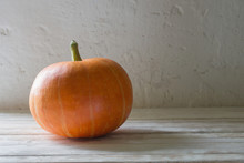 Orange Pumpkin On Wooden Table On Background Old White Wall