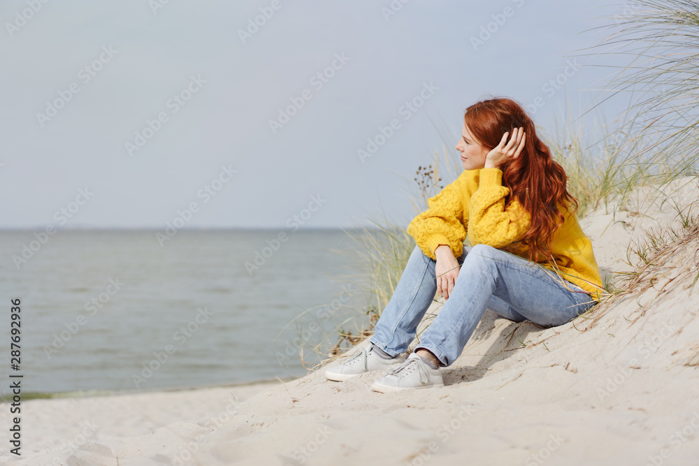 Fototapeta Pensive young woman sitting relaxing on a beach