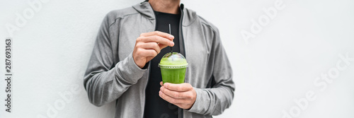 Green juice detox drink healthy man drinking green smoothie cup protein shake panoramic banner. Vegan meal replacement diet at cafe. Spinach morning breakfast panorama. Healthy eating lifestyle.