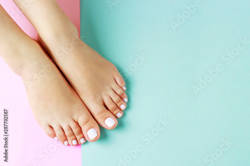 Wall Murals Pedicure Female legs with white pedicure on pink and blue background, top view