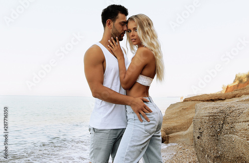 Obraz beautiful lovely couple wearing jeans,posing at summer beach - fototapety do salonu
