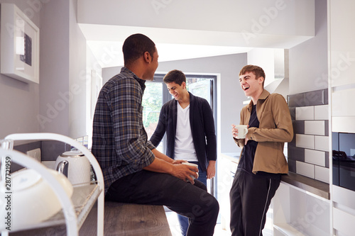 Photo Group Of Male College Students In Shared House With Hot Drinks In Kitchen Hangin