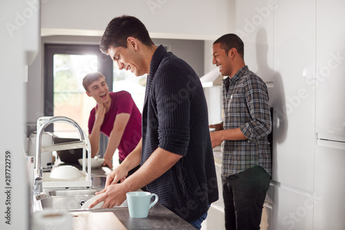 Ingelijste posters Eigen foto Group Of Male College Students In Shared House Kitchen Washing Up And Hanging Out Together