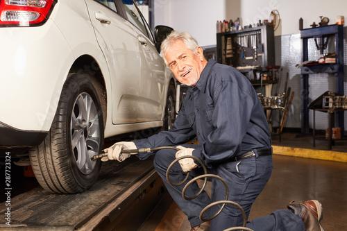Vászonkép  Senior als KFZ Mechaniker beim Reifenwechsel