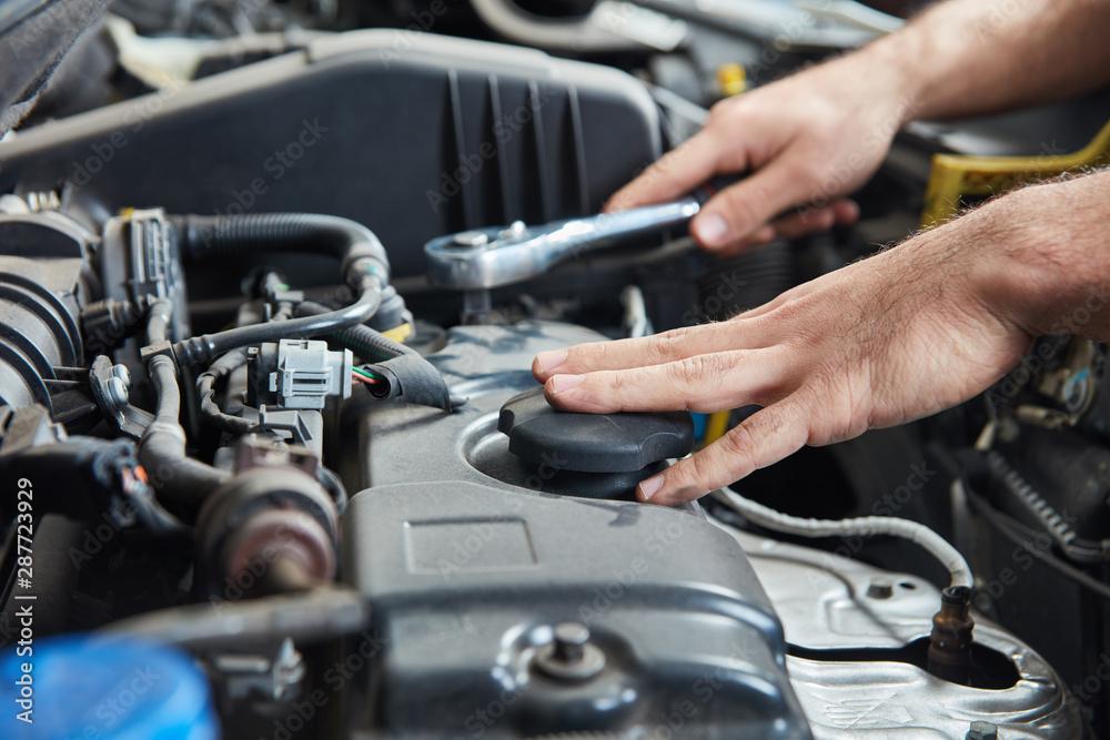 Fototapeta Hand mit Werkzeug am Auto Motor bei Inspektion