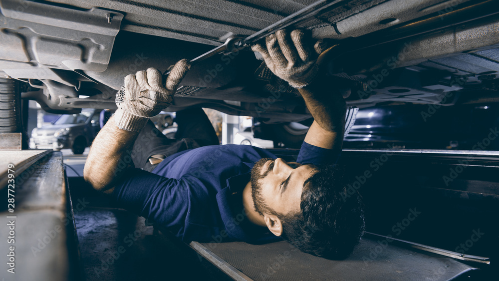 Fototapeta Mechatroniker bei Unterboden Reparatur am Auto