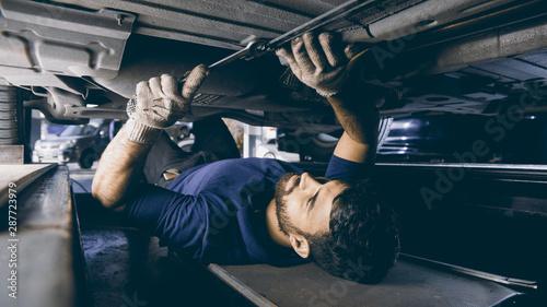 obraz dibond Mechatroniker bei Unterboden Reparatur am Auto