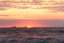 Dawn At The Sea. The Sun Is Rising Over The Horizon And The Silhouettes Of Ships On The Horizon. Soft Selective Focus.
