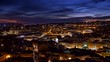 Lisbon, Portugal. Panoramic shot of post sunset evening city. Buildings and houses illuminated with yellow light
