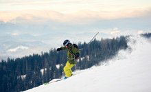 Proficient Skier With Backpack Racing Down From High Slope. Concept Of Popular Winter Extreme Amateur Sport. Active Lifestyle In Winter. Amazing Nature Mountains View From High Ski Slope. Side View