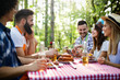 canvas print picture - Group of happy friends eating and drinking beers at barbecue dinner