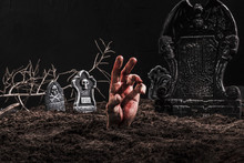 Hand Sticking Out Grave On Dark Cemetery