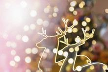 Abstract Blurry Golden Bokeh Effect With Decoration Of Two Golden Reindeer For Christmas Eve.