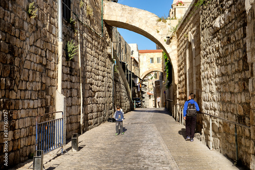 Fototapeten Schmale Gasse Kids go to school along narrow stone street in Old City of Jerusalem, Israel. May 2017
