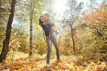 Walking And Playing Young Mother With Her Baby Outdoors. Mom And Son In An Autumn Park