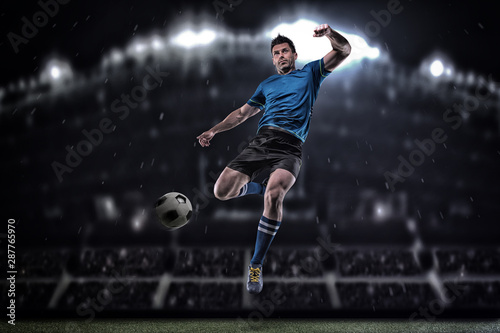 Fotografie, Obraz Soccer player in action on a dark background