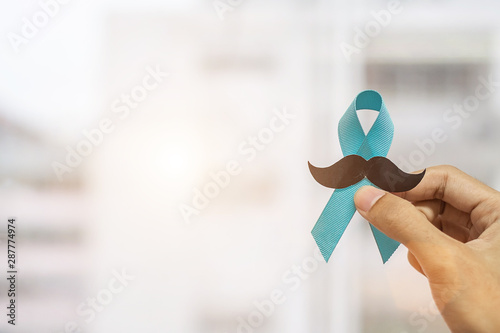 Photo November Prostate Cancer Awareness month, Man holding Blue Ribbon with mustache  for supporting people living and illness