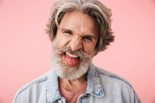 Portrait Of Amusing Old Man With Gray Beard Grimacing And Sticking Out His Tongue At Camera