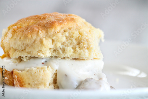 Fototapeta American biscuits from scratch served with thick white sausage gravy. Selective focus against white background. obraz