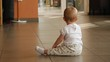 Toddler baby girl crawl on the tile floor of food court interior public place