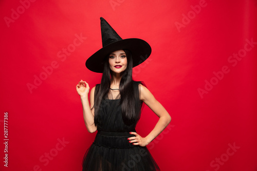 Young brunette woman in black hat and costume on red background Fototapet