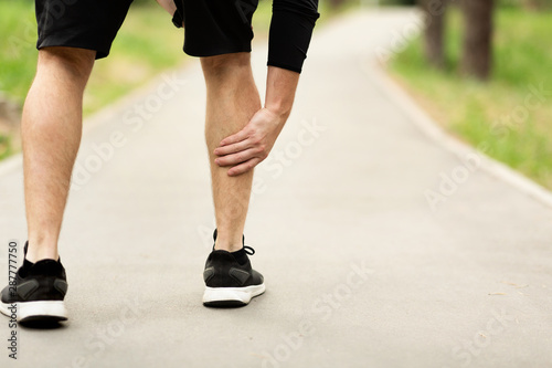 Canvas Print Male runner is suffering from calf pain on jogging