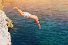 Young Man Jumping Off Cliff Into Blue Water Ocean At Sunset. Active Outdoor, Holiday Adventure, Tourism Action, Healthy Summer Joy, Fun Activity Lifestyle. Crazy Adult Guy In Swimwear Fly From Climb.