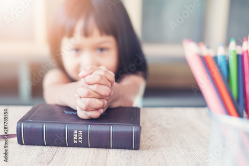 Fotografie, Obraz  Little Asian girl pray with bible in classroom at school, bible study concept