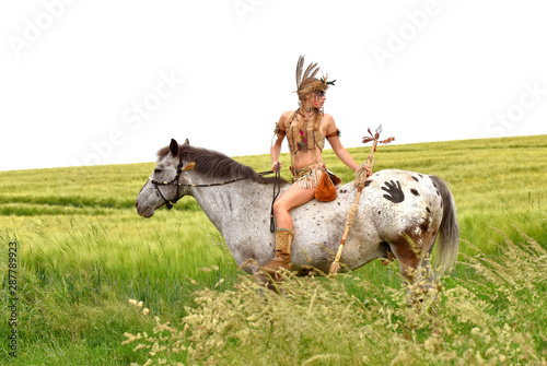 Tela A young Indian girl rides her pony through the prairie grass