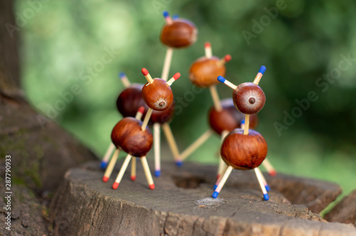 Foto auf AluDibond Reh Group of funny chestnut animals on tree stump, green background, traditional autumn handcraft, European roe deer with family