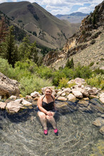 Blonde Woman Wearing A Polka Dot Swimsut Soaks And Enjoys The Goldbug Hot Springs In The Salmon Challis National Forest Of Idaho