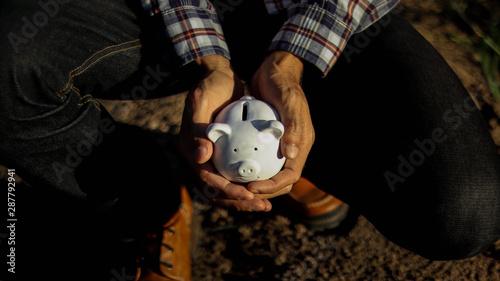 Fototapeta Small white piggy bank in a hands in the morning obraz na płótnie