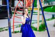 beautiful girl in a long dress on a swing