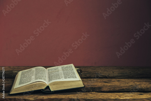 Fotografie, Obraz  Beautiful open Holy Bible on old oak wooden table and dark red wall background
