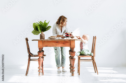Fotografie, Tablou  Pretty young mother a confectioner works on maternity leave at home and feeds his capricious little child refusing to eat